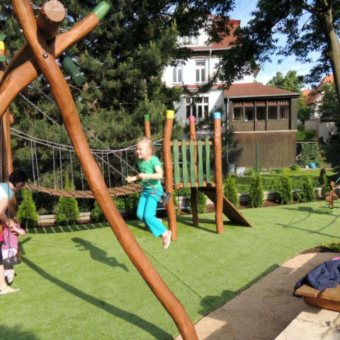 Děti v na novém dětském hřišti z akátového dřeva a umělou trávou